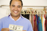 Hispanic man holding cash in clothing store
