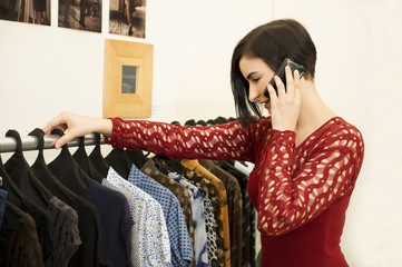 Hispanic woman talking on cell phone in clothing store