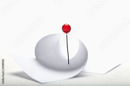 Red pin securing paper