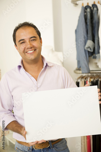 Hispanic man holding blank sign in clothing store