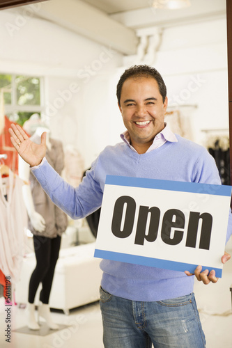 Hispanic man holding open sign in clothing store