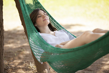 Very relaxed woman sleeping in a hammock outdoors