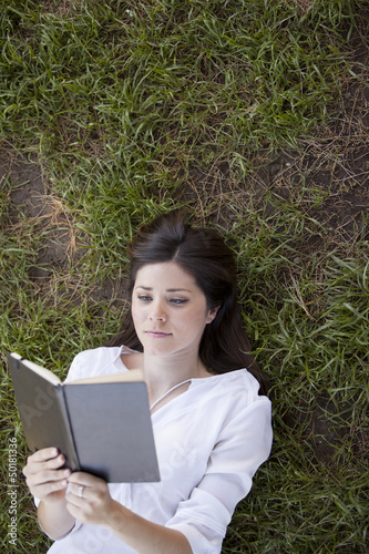 Pretty girl reading a book while laying on the grass at a park