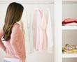 Hispanic woman looking at clothing in closet
