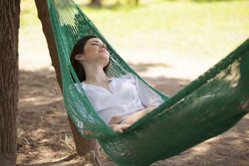 Gorgeous girl sleeping in a hammock outdoors