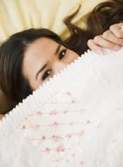Playful Hispanic woman underneath blanket