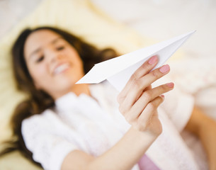 Hispanic woman holding paper airplane
