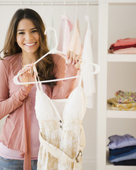 Hispanic woman holding dress on hanger
