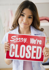 Hispanic woman holding closed sign in store