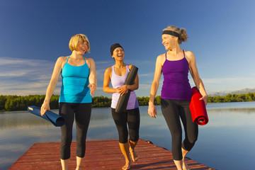 Women carrying yoga mats on lake pier