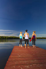 Women holding yoga mats on lake pier