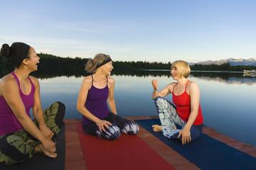 Woman practicing yoga on lake pier