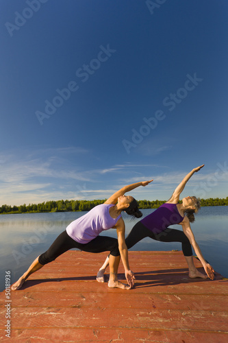 Women stretching on lake pier