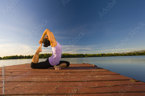 Korean woman practicing yoga on lake pier