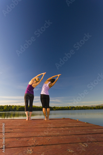 Woman practicing yoga on lake pier