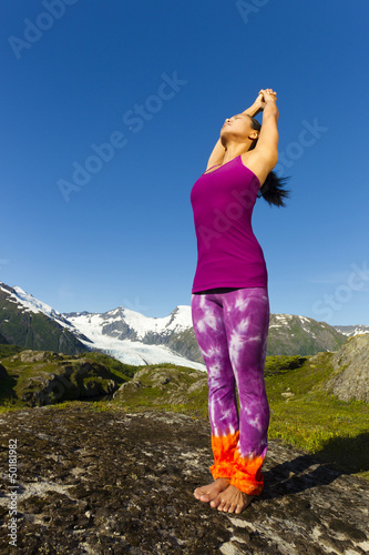 Korean woman stretching with mountains in background