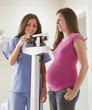Nurse weighing pregnant woman