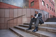 Businessman sitting on stairs text messaging on cell phone
