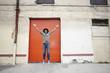 Excited Black man jumping on sidewalk