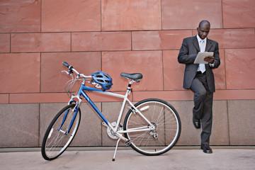Businessman using digital tablet near bicycle