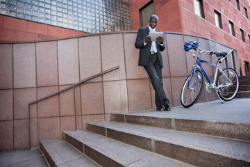 Businessman standing near bicycle using digital tablet