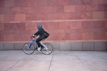 Businessman riding bicycle on sidewalk