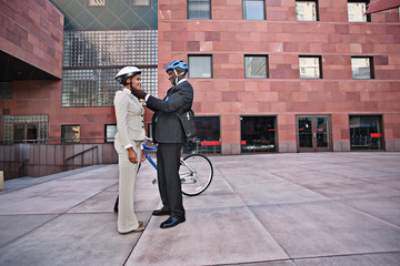 Businessman putting bicycle helmet on girlfriend