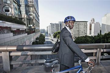 Businessman pushing bicycle over urban bridge