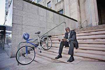 Businessman sitting on stairs using digital tablet