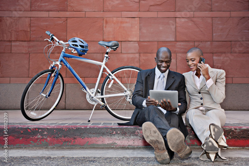 Business people sitting on curb using digital tablet and cell phone