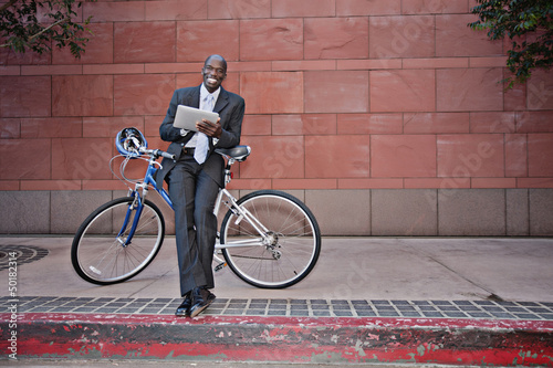 Businessman leaning on bicycle using digital tablet