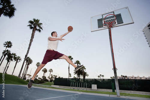 Caucasian man playing basketball outdoors