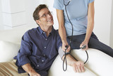 Caucasian woman taking husband's blood pressure