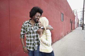 Couple hugging on urban sidewalk