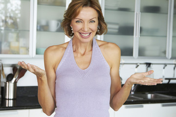 Smiling Caucasian woman standing in kitchen