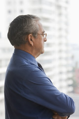 Serious Hispanic businessman looking out window