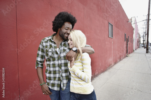 Couple hugging on urban sidewalk