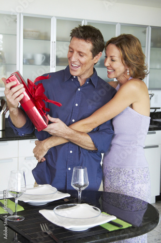 Caucasian woman giving husband a gift