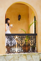 Pacific Islander woman drinking coffee on patio