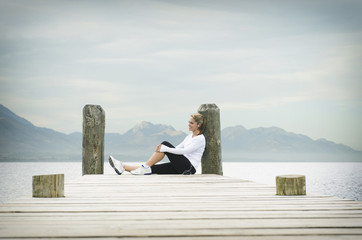 Hispanic woman sitting on pier