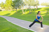 Hispanic woman stretching on path