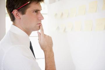 Caucasian businessman looking at adhesive notes