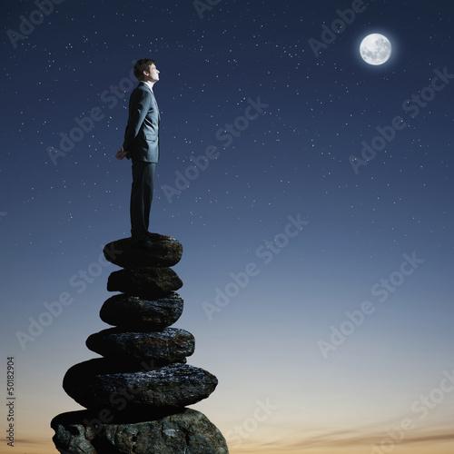 Caucasian businessman standing on pile of rocks at night