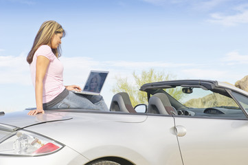 Hispanic woman sitting in convertible sports car with laptop