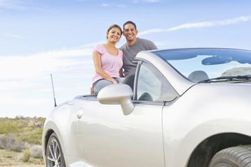 Hispanic  couple sitting in convertible sports car