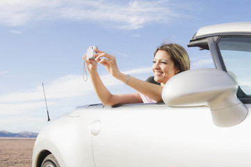 Hispanic woman in sports car taking photograph