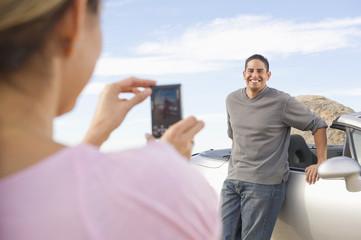 Hispanic woman taking photograph of husband next to sports car