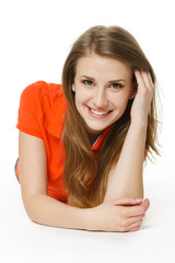 Young woman lying on the studio floor smiling at you