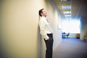 Caucasian businessman leaning against office wall