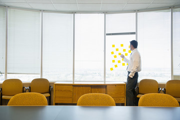 Caucasian businessman putting adhesive notes on window